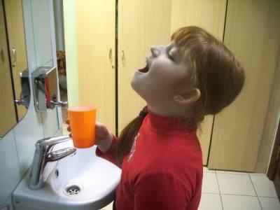 Девочка полоскает горло ромашкой